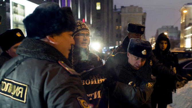 Russian police officers detain a protester outside the Federation Council Wednesday, Dec. 26, 2012. Several protesters were detained Wednesday morning outside the upper chamber of Russia's parliament which is set to vote on a measure banning Americans from adopting Russian children. (AP Photo/Alexander Zemlianichenko)