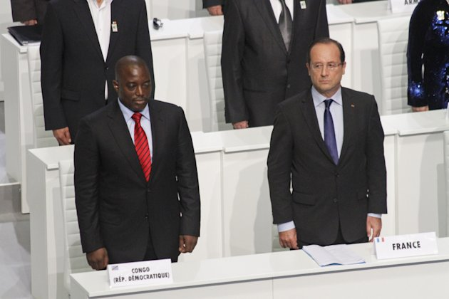 French President Francois Hollande, right, and Congolese President Joseph Kabila stand during the opening session of the Francophonie Summit, in Kinshasa, Congo, Saturday, Oct. 13, 2012. Hollande is taking part in a summit of French-speaking countries, after months of controversy surrounding his visit to the vast Central African nation. He initially threatened not to attend but ultimately confirmed his participation in July, saying he wants to break away from the traditional paternalistic ways of France toward Africa. (AP Photo/John Bompengo)