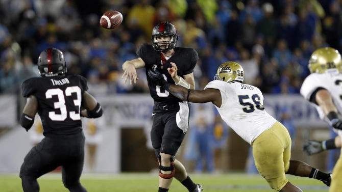 Stanford quarterback Kevin Hogan throws under pressure from UCLA defensive end Datone Jones (56) during the first half of the Pac-12 championship NCAA college football game in Stanford, Calif., Friday, Nov. 30, 2012. (AP Photo/Marcio Jose Sanchez)