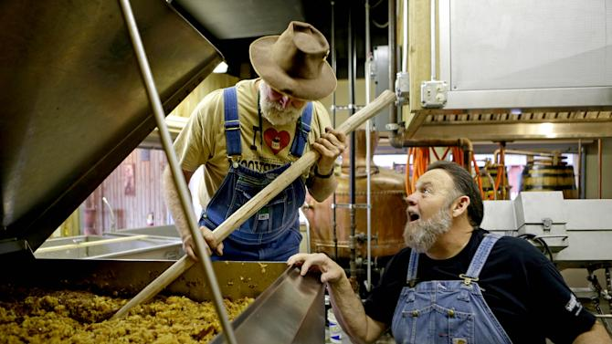 In this Friday, Nov. 16, 2012 photo, distillers Dwight Bearden, right, and Bob Suchke look over a batch of fermented apple brandy mash as they make moonshine in the Dawsonville Moonshine Distillery in Dawsonville, Ga. Distillers are making their first batches of legal liquor in this tiny Georgia town's hall, not far from the mountains and the maroon, orange and gold canopy of trees that once hid bootleggers from the law. (AP Photo/David Goldman)