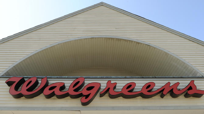 FILE - The sign above a Walgreens entrance, is seen in this Monday, Sept. 28, 2009 file photo taken in Gloucester, Mass. Walgreen Co. will become the latest big employer to send its workers shopping for their health insurance coverage instead of providing a few plan choices for them. The nation's largest drugstore chain said Wednesday Sept. 18, 2013 that it will start giving workers a contribution toward the cost of coverage and then send them to a private health insurance exchange where they will pick from as many as 25 plans. Walgreen currently offers its workers two to four options depending on where the employee lives. (AP Photo/Lisa Poole, File)