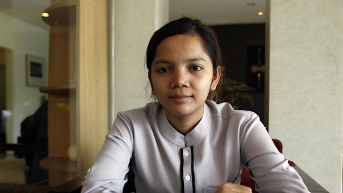 In this July 28, 2014, photo, Sok Sambour, 25, works as a receptionist at a hotel after graduating from accounting school. Her parents told her about that era, including exactly how long the Khmer Rouge rule lasted: three years, eight months and 20 days. An elderly neighbor told her that just catching a fish to eat was enough to be accused of betrayal and face almost certain execution. A U.N.-assisted genocide tribunal will deliver a verdict this coming Thursday in the trial of the two top leaders of the communist Khmer Rouge, whose extremist policies in the late 1970s are blamed for the deaths of an estimated 1.7 million Cambodians though starvation, medical neglect, overwork and execution. (AP Photo/Heng Sinith)