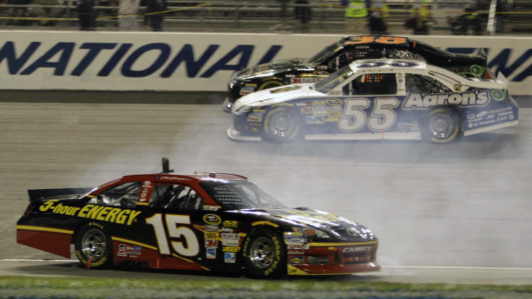 Clint Bowyer (15) spins out in front of Martin Truex Jr., (55) and David Gilliland (38) during the NASCAR Sprint Cup Series auto race at the Richmond International Raceway in Richmond, Va., Sunday, Sept. 9, 2012. (AP Photo/Steve Helber)
