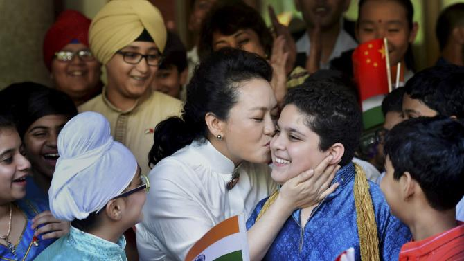 Visiting Chinese President Xi Jinping's wife Peng Liyuan kisses a student during a visit to the Tagore International School in New Delhi, India, Thursday, Sept. 18, 2014. Indian and Chinese troops faced off along their Himalayan border on Thursday as the countries' leaders held a rare meeting in New Delhi, promising to boost economic cooperation and substantially increase Chinese investment in India's infrastructure.(AP Photo/ Press Trust of India) INDIA OUT