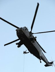 British Royal Marine Commando Martyn Williams abseils with the Olympic Flame from a helicopter doen to the Tower of London