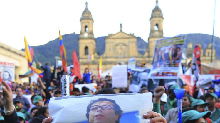 A demonstrator holds a newspaper with a picture of Bogota's mayor Petro during a protest at Bogota's Bolivar Square