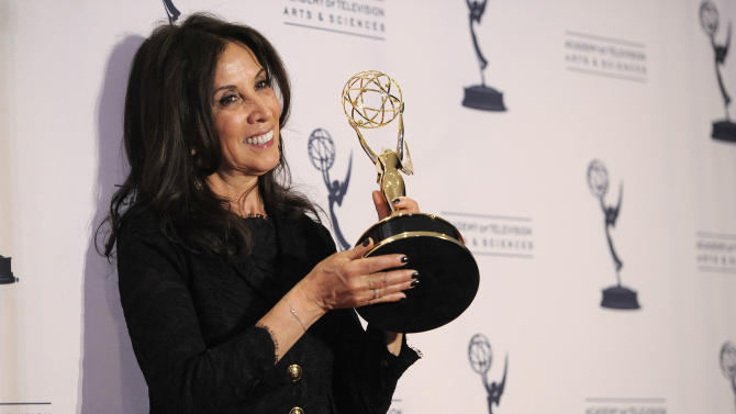 """Olivia Harrison poses backstage with the award for outstanding nonfiction special for """"George Harrison: Living in the Material World"""" at the 2012 Creative Arts Emmys at the Nokia Theatre on Saturday, Sept. 15, 2012, in Los Angeles. (Photo by Chris Pizzello/Invision/AP)"""
