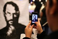 <p>A man uses an iPhone to photograph a painting of the late Apple co-founder Steve Jobs. Some analysts thought Apple might bring in a celebrity to infuse the Wednesday media event with magical energy that has been missing in the absence of Jobs, who died last year.</p>