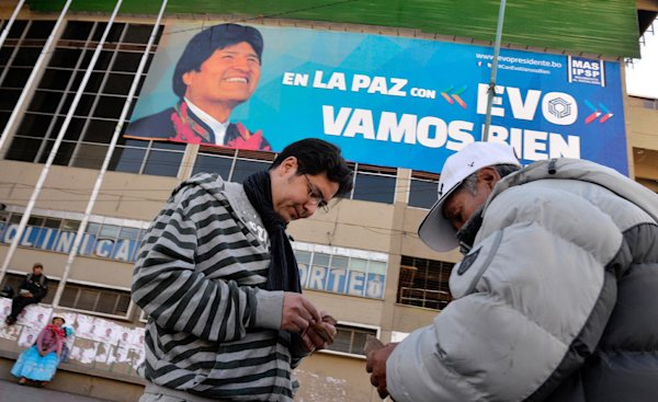 Two men change currency under a gigantic electoral campaign billboard