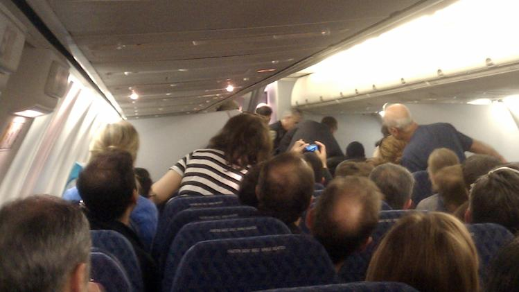In this image captured by citizen journalist Andrew Wai, passengers, top right, subdue a man identified as Rageh Almurisi (not seen) on board an American Airlines flight headed to San Francisco, Sunday, May 8, 2011. Federal investigators are looking into the background of Almurisi , a Northern California man with a Yemeni passport, who pounded on the cockpit door of an American Airlines flight as it approached San Francisco on Sunday evening. (AP Photo/Andrew Wai)