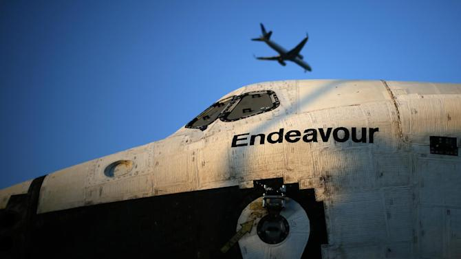 A plane flies over the Space Shuttle Endeavour as it is moved down the street, Saturday, Oct. 13, 2012 in Los Angeles. Endeavour's 12-mile road trip kicked off shortly before midnight Thursday as it moved from its Los Angeles International Airport hangar en route to the California Science Center, its ultimate destination. (AP Photo/Lucy Nicholson, Pool)