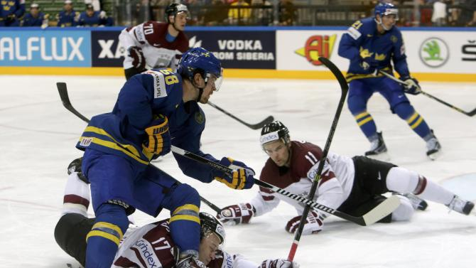 Latvia's Saulietis and Sotnieks fall as Sweden's Lander passes during their Ice Hockey World Championship game at the O2 arena in Prague