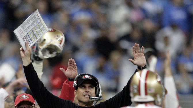 San Francisco 49ers head coach Jim Harbaugh signals a touchdown after watching the stadium television replay Delanie Walker's touchdown in the fourth quarter of an NFL football game against the Detroit Lions, Sunday, Oct. 16, 2011 in Detroit. The Lions called for a review and the replay confirmed the touchdown called on the field. (AP Photo/Duane Burleson)
