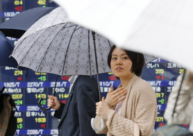 People under umbrellas walk by an electronic stock board of a securities firm in Tokyo, Monday, May 20, 2013. Japan's Nikkei 225 index jumped 1.4 percent to 15,352.84 as evidence of a steady economic