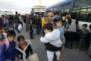 A Syrian man holds his two children as the other two…