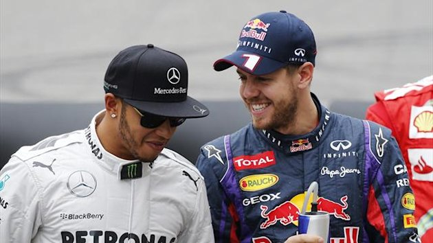 Red Bull Formula One driver Sebastian Vettel (R) of Germany talks with Mercedes Formula One driver Lewis Hamilton of Britain (Reuters)