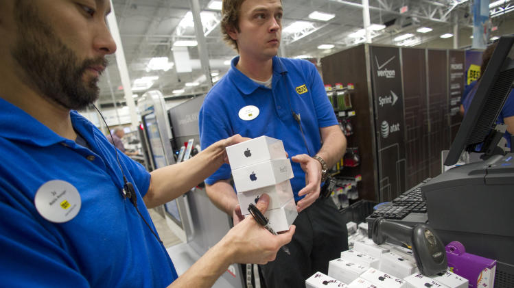 FILE - In this Sept. 20, 2013 file photo, Managers Ju Lee, left, and Brad Deep get iPhone 5s and iPhone 5c phones ready for sale on the day of their release, at a Best Buy in Atlanta. Apple's quarterly earnings are still sagging even as the sales of its iPhones are rising, a vexing phenomenon feeding investor worries about whether stiffer competition in the mobile device market will continue to undercut the company's prosperity. (AP Photo/John Amis, File)