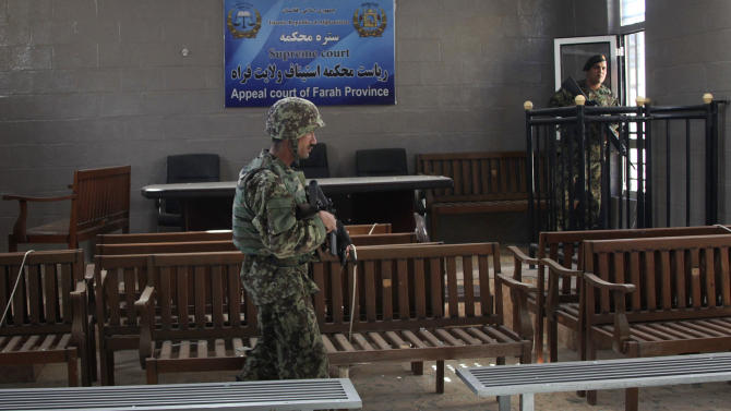 Afghan Army soldiers search the main courtroom in the destroyed courthouse in Farah, western Afghanistan, Thursday, April 4, 2013. Suicide bombers disguised as Afghan soldiers stormed a courthouse Wednesday in a failed bid to free more than a dozen Taliban prisoners in western Afghanistan, officials said. Scores of people, including the attackers were reported killed in the fighting. The assault in Farah province was the latest example of the Taliban's ability to strike official institutions despite tight security measures. (AP Photo/Hoshang Hashimi)