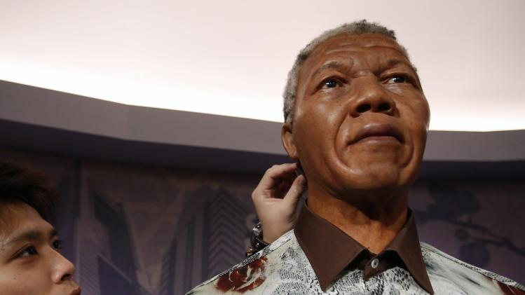 A visitor touches a wax figure of Mandela at the Madame Tussauds wax museum in Tokyo