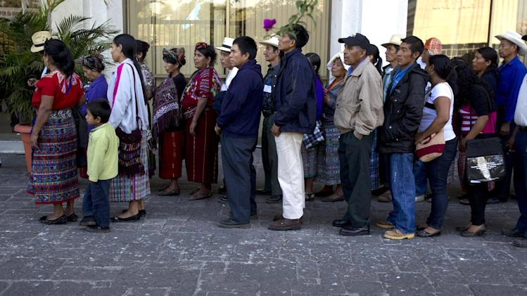 The relatives of victims of a massacre of Indians from the Ixil ethnic group line up to enter the court where Guatemala's former dictator Jose Efrain Rios Montt is to stand trial on genocide charges in Guatemala City, Tuesday, March 19, 2013. Prosecutors hope to painstakingly prove through a detailed recreation of the military chain of command that Gen. Efrain Rios Montt must have had knowledge of the massacres of Mayan Indians and others in the Guatemalan highlands during one of the bloodiest phases of the country's long civil war. Because he held absolute power over the U.S.-backed military government, his failure to stop the slaughter is proof of his guilt, prosecutors and lawyers for victims say. (AP Photo/Moises Castillo)