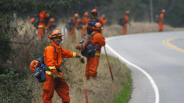 Inmates from the Gabilan Conservation Camp are deployed along Highway 1 to hold a fire line during a burn out operation in Big Sur