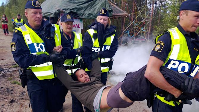 An environmental activist is carried away by Swedish police officers during a protest near the site of a proposed iron ore mine in Jokkmokk, Sweden, Wednesday, Aug. 21, 2013. Police removed some 50 screaming and singing activists who were blocking a road in northern Sweden in a protest against a British mining company's plans to build an iron ore mine in the area. (AP Photo/David MacDougall)