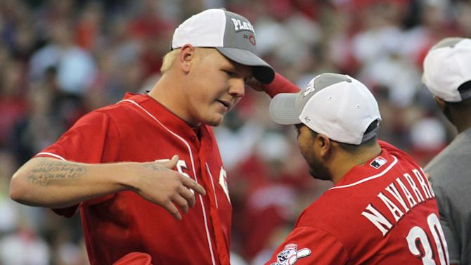 Cincinnati Reds starting pitcher Mat Latos, left, hugs catcher Dioner Navarro (30) after they defeated the Los Angeles Dodgers 6-0 to clinch the National League Central Division in a baseball game on Saturday, Sept. 22, 2012, in Cincinnati. Latos pitched eight scoreless innings to earn the win. (AP Photo/Tom Uhlman)