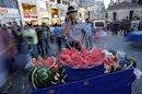 A street vendor selling watermelons talks on his mobile phone as he waits for customers at Taksim square in central Istanbul