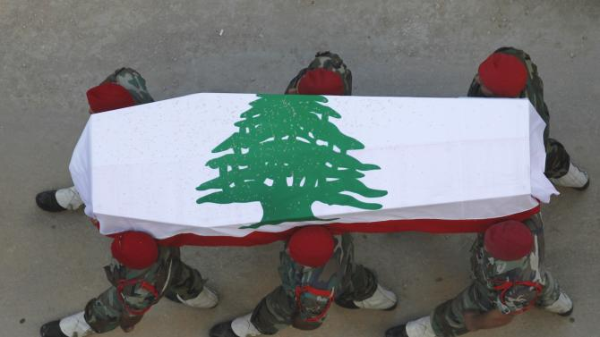 Lebanese soldiers carry the coffin of their comrade, who was killed by a roadside bomb, during his funeral in Sidon
