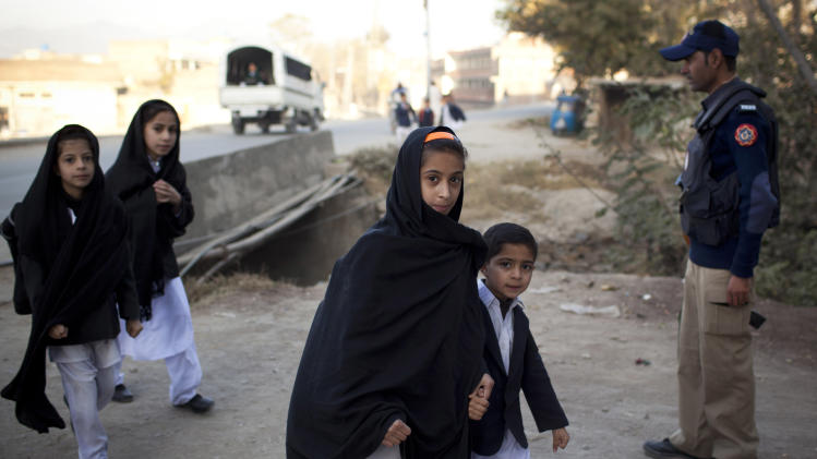 In this Thursday, Nov. 15, 2012 photo, A local policeman secures the road as young Pakistani children make their way up to the Khushal School for Girls in Mingora, Swat Valley Pakistan. Malala Yousufzai attended Khushal School when a Taliban gunman shot her and her two friends, Shazia Ramazan and Kainat Riaz. Malala was shot for her outspoken insistence on girls education. Shazia and Kainat are to return to school this week for the first time since the shooting more than one month ago. ( AP Photo/Anja Niedringhaus)