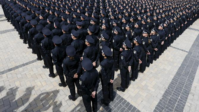 Police officers attend an oath-taking ceremony, which started up the work of a new police patrol service, in Kiev