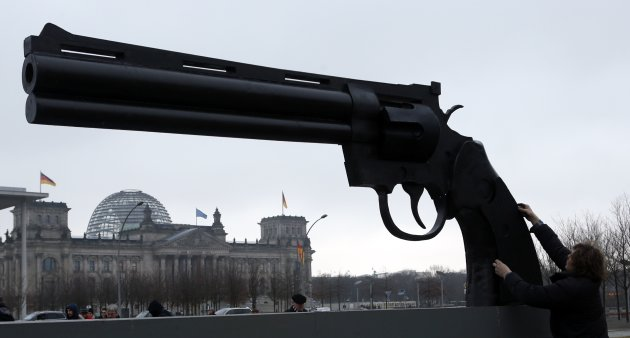 "A worker makes final touches on a sculpture showing a pistol, inspired by Swedish artist Carl Frederik Reutersvaerd sculpture's ""Non-Violence"", in front of the Reichstag's building in Berlin"