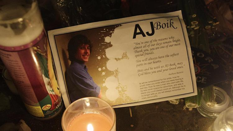 A photo and tribute to movie theater shooting victim AJ Boik is shown next to a lit candle, Saturday, July 21, 2012, at a memorial to the shooting victims in Aurora, Colo. (AP Photo/Ted S. Warren)