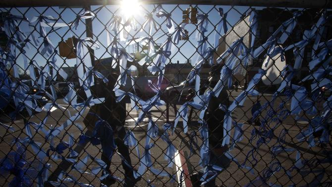 People walk past a fence covered in blue ribbons as a makeshift tribute near Christ Tabernacle Church in the Queens borough of New York