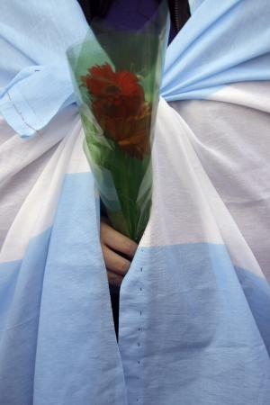 A woman wrapped in an Argentine flag holds flowers as she waits to pay her last respects to former President Nestor Kirchner at the government palace in Buenos Aires, Argentina,  Thursday Oct. 28, 2010.  Former President Nestor Kirchner, the husband of Argentina's current President Cristina Fernandez, died Wednesday after suffering a heart attack. He was a likely candidate in next year's presidential elections. (AP Photo/Natacha Pisarenko)