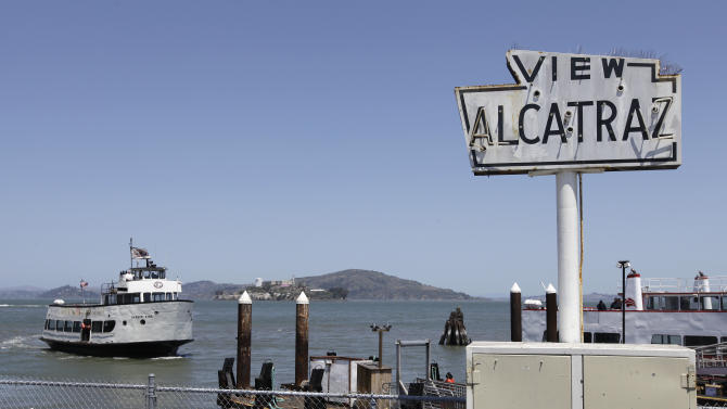 In this photo taken Thursday, May 24, 2012, a harbor cruise boat makes it way back to Fisherman's Wharf with Alcatraz Island in the background in San Francisco. (AP Photo/Eric Risberg)