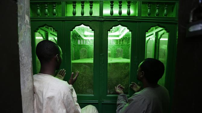In this Friday, June 7, 2013 photo, men pray at the shrine of Al Sayyid Ali bin Mohammed bin Ja'far al-Sadiq in Cairo, Egypt. Egypt's roughly 15 million Sufi Muslims say their places of worship are under threat by rising radicalism. They say that since the country's 2011 uprising that toppled longtime autocrat Hosni Mubarak, shrines held sacred to them have been attacked by hardliners who deem them heretical and idolatrous. (AP Photo/Hassan Ammar)