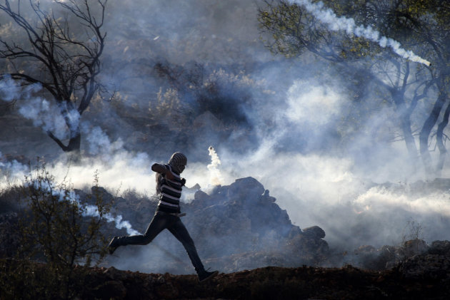 A Palestinian demonstrator runs through a cloud of tear gas during clashes against Israel's operations in Gaza Strip, outside Ofer, an Israeli military prison near the West Bank city of Ramallah, Thur