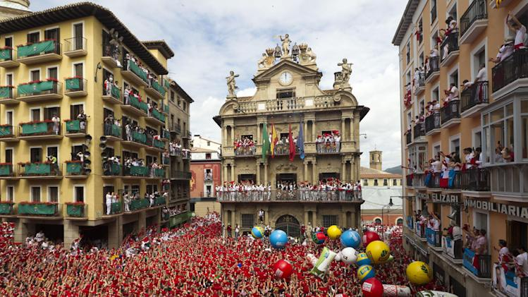 Revelers hold up traditional red neckties during the 'Chupinazo', the official opening of the 2012 San Fermin fiestas, Friday, July 6, 2012 in Pamplona, Spain. Revelers from around the world kick off the San Fermin festival with a messy party in the Pamplona town square, one day before the first of eight days of the running of the bulls. (AP Photo/Daniel Ochoa de Olza)