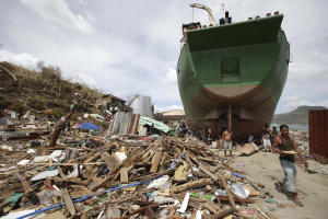 A survivor walks beside a ship that was washed ashore…