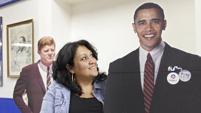 In this Sept. 22, 2011 photo, Christine Alonzo stands with cutouts of Presidents Barack Obama and John F. Kennedy at the Democratic Headquarters in Pueblo, Colo. People like Alonzo are keeping Obama afloat and giving his political team hope that he can win re-election, despite high unemployment and sour attitudes toward his policies and the country's future. Alonzo volunteered for Obama during the 2008 campaign. A few months after Obama's victory, she lost her job. She's still looking for work. Instead of blaming Obama for the economic crisis, she's volunteering full time to help him capture a second term. (AP Photo/Ed Andrieski)