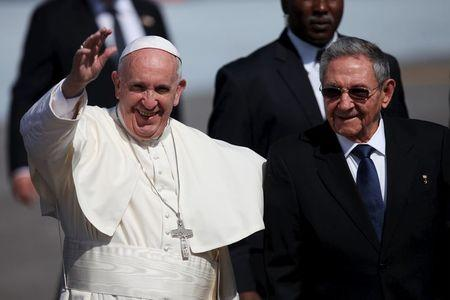 Pope Francis (L), waves to journalists as he walks beside Cuba's President Raul Castro after his arrival at the Jose Marti International Airport in Havana