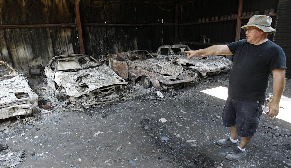 Car collector John Chapman surveys the losses at his home, Tuesday, Sept. 6, 2011, in Bastrop, Texas. Chapman lost more than 175 cars to the wildfires. (AP Photo/Eric Gay)