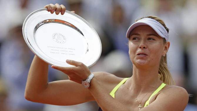 Russia's Maria Sharapova holds the runner-up trophy after losing to Serena Williams of the U.S. in two sets 4-6, 4-6, in the women's final of the French Open tennis tournament, at Roland Garros stadium in Paris, Saturday June 8, 2013.  (AP Photo/Petr David Josek)