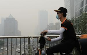 A cyclist wears a mask in Beijing, covered by heavy…