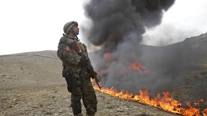 An Afghan counternarcotic policeman (CNPA) secures the area as 25 tons of drugs and drug-making gear are burned on the outskirts of Kabul, Afghanistan, Sunday, Oct. 14, 2012. The 25 tons of drugs and paraphernalia where confiscated over the past nine months in the Kabul area. (AP Photo/Ahmad Jamshid)