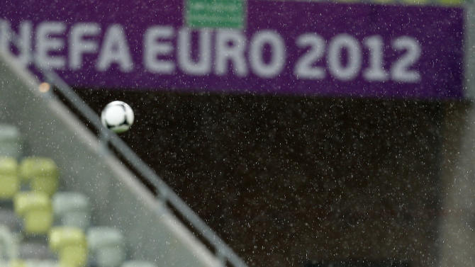 Greece's coach Fernando Santos stands under the heavy rain during a training session, prior to the Euro 2012 soccer quarterfinal match between Germany and Greece, at PGE Arena in Gdansk, Poland on Thursday, June 21, 2012. (AP Photo/Thanassis Stavrakis)
