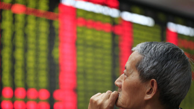 An investor looks at the stock price monitor at a private securities company Friday, June 7, 2013 in Shanghai, China. Asian stock markets fell Friday, ignoring a rebound on Wall Street, as investors stayed on the sidelines ahead of a key U.S. jobs report later in the day. (AP Photo)
