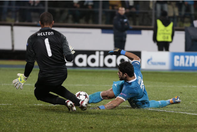 Zenit's Hulk, right. shoots at goal as Porto's goalkeeper Helton closes in to block during the Champions League group G soccer match between Zenit and Porto at Petrovsky stadium in St.Petersburg, Russ