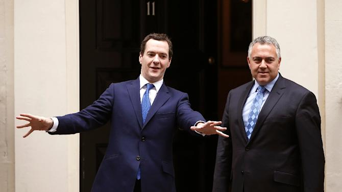 Britain's Chancellor of the Exchequer George Osborne (L) welcomes Australia's Treasurer Joe Hockey, outside No. 11 Downing Street in London, on October 14, 2014